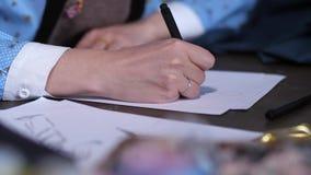 Mano del bosquejo del dibujo del diseñador de ropa almacen de metraje de vídeo