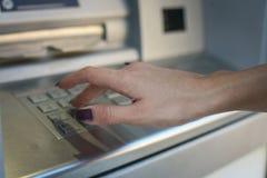 Mano del código de seguridad de la mujer que mecanografía en el cajero automático Foto de archivo libre de regalías