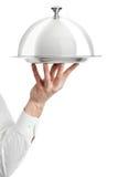 Mano del camarero con la tapa del cloche Fotografía de archivo