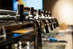 Mano del camarero que vierte una cerveza de cerveza dorada grande en golpecito Resto en una barra con los amigos imagen de archivo