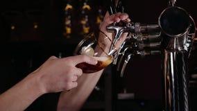 Mano del camarero que vierte una cerveza de cerveza dorada grande en golpecito en un restaurante o un pub almacen de video