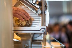 Mano del carnicero que corta el salami fotografía de archivo libre de regalías