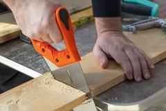 Mano del carpintero con el handsaw que corta a los tableros de madera imagen de archivo