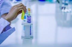 Mano del chimico Holds un tubo chimico da sperimentare con i liquidi variopinti in tubi di vetro disposti sulla tavola immagini stock libere da diritti