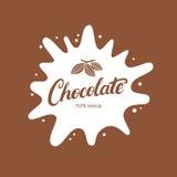 Mano del chocolate escrita poniendo letras al logotipo, al emblema, a la insignia o a la etiqueta con el chapoteo y el grano de c Fotografía de archivo libre de regalías