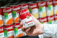 Mano del cliente che tiene un barattolo di latta della minestra del pomodoro di Campbell's fotografie stock