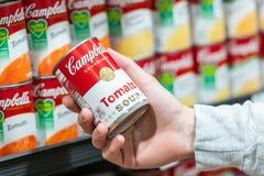 Mano del cliente che tiene un barattolo di latta della minestra del pomodoro di Campbell's immagini stock