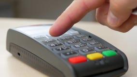 Mano del cliente que paga con la tarjeta de crédito sin contacto con tecnología de NFC almacen de metraje de vídeo