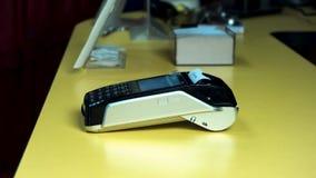 Mano del cliente que paga con la tarjeta de crédito sin contacto con tecnología de NFC Camarero con una máquina del lector de la  almacen de metraje de vídeo