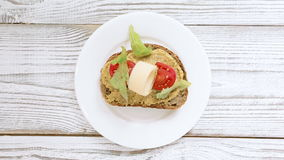 Mano del cocinero que hace el bocadillo con la salsa, los tomates, el parmesano del queso y el arugula para el desayuno y el almu metrajes