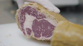 Mano del cocinero que sostiene la carne congelada cubierta con la cubierta amarilla que miente en el cierre de la tabla para arri almacen de video