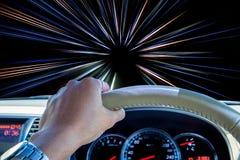 Mano del conductor que sostiene el volante con las líneas ligeras fondo del movimiento abstracto de la velocidad Imagen de archivo