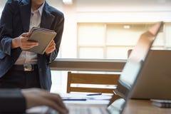 Mano del cuaderno del control del hombre de negocios con el compañero de trabajo en la oficina, proje imagen de archivo