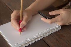 Mano del cuaderno de la escritura de la mujer y del smartphone de la mirada en de madera imagenes de archivo
