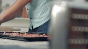 Mano del cuoco unico che dispone gli ingredienti sulla pizza video d archivio