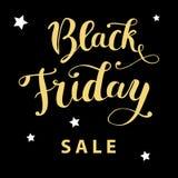 Mano del ` de la venta de Black Friday del ` que pone letras al texto de oro en un fondo negro Foto de archivo