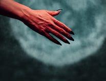 Mano del diavolo con il gesto della stretta di mano alla mezzanotte Fotografia Stock