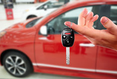 Mano del distribuidor autorizado con una llave del coche Foto de archivo libre de regalías