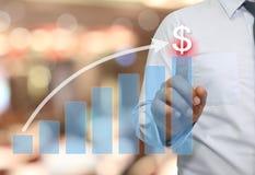 Mano del dito di uso dell'uomo d'affari che indica la cima del grafico Immagine Stock