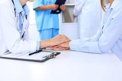 Mano del doctor que tranquiliza a su paciente femenino Los éticas médicos y concepto de la confianza imágenes de archivo libres de regalías