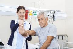 Mano del dottore Examining Senior Man femminile Fotografia Stock Libera da Diritti