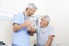 Mano del dottore Examining Senior Man nel centro di riabilitazione Immagini Stock