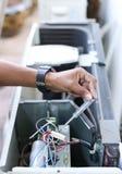 Mano del electricista que sostiene un detector en un eléctrico Fotos de archivo libres de regalías