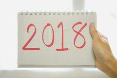 Mano del fondo de la Feliz Año Nuevo del papel del control de la mujer con el mensaje Foto de archivo