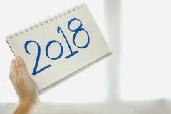 Mano del fondo de la Feliz Año Nuevo del papel del control de la mujer con el mensaje Fotografía de archivo libre de regalías