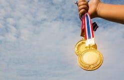 Mano del ganador aumentada y que sostiene dos medallas de oro con la cinta tailandesa imagen de archivo libre de regalías