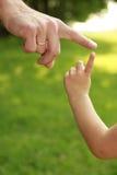 Mano del genitore e del bambino in natura Fotografia Stock