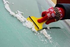 Mano del ghiaccio di raschio della donna dal tergicristallo dell'automobile Fotografia Stock Libera da Diritti