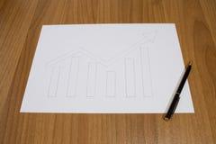 Mano del gráfico de negocio dibujada con una pluma en una tabla Imágenes de archivo libres de regalías