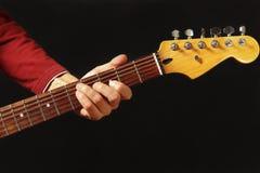 Mano del guitarrista de la roca detrás del cuello de la guitarra eléctrica en fondo negro Imagen de archivo