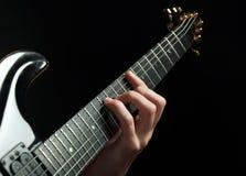 Mano del guitarrista que toca la guitarra sobre negro Fotos de archivo libres de regalías