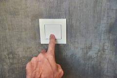 Mano del hombre, apagar la luz, interruptor, vista delantera fotografía de archivo