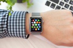 Mano del hombre con el reloj de Apple e icono del app en la pantalla Imagen de archivo libre de regalías