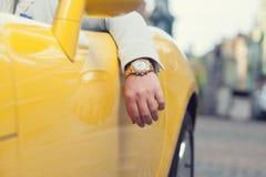 Mano del hombre con el reloj de oro en coche Fotografía de archivo libre de regalías