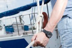 Mano del hombre con la cuerda de barco dueño de un yate que ata el nudo del mar los relojes del negro en hombre dan llevar a cabo imagen de archivo
