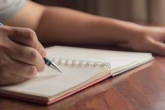 Mano del hombre con la escritura de la pluma en el cuaderno Foto de archivo