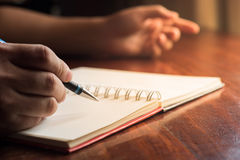 Mano del hombre con la escritura de la pluma en el cuaderno Imagen de archivo libre de regalías