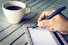 Mano del hombre con la escritura de la pluma en el cuaderno Café y cuaderno en la tabla de madera Imágenes de archivo libres de regalías