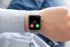 Mano del hombre con llamada del reloj y de teléfono de Apple en la pantalla Foto de archivo
