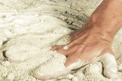 Mano del hombre con los fingeres enterrados en arena Fotografía de archivo libre de regalías
