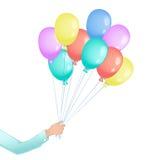 Mano del hombre con los globos que vuelan coloreados Fotos de archivo