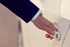 Mano del hombre de negocios que abre una puerta de coche Imágenes de archivo libres de regalías