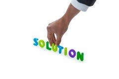 Mano del hombre de negocios que arregla palabra de la solución Imagen de archivo libre de regalías