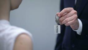 Mano del hombre de negocios que da llaves de la mujer a la riqueza, compartiendo secretos del primer del éxito metrajes