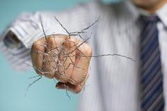 Mano del hombre de negocios que golpea el vidrio transparente con agrietado Imágenes de archivo libres de regalías