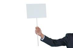 Mano del hombre de negocios que lleva a cabo el cartel en blanco Imagenes de archivo